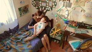 Lúcia (Ingra Lyberato) acorda o filho, Vinci (Lucca Rocha).